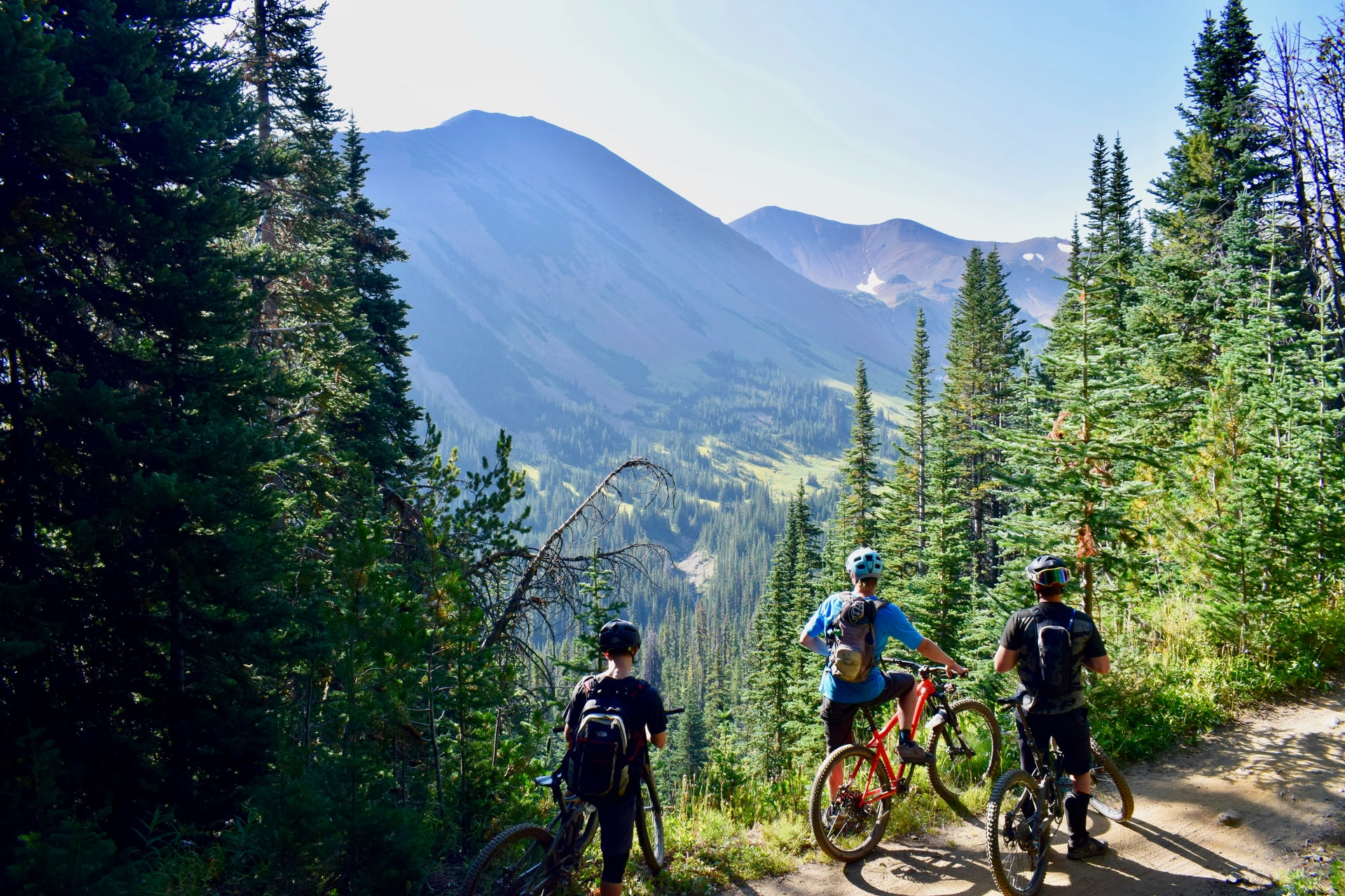 three cyclists with biking backpacks riding on bicycles during daytime in Canadian mountains