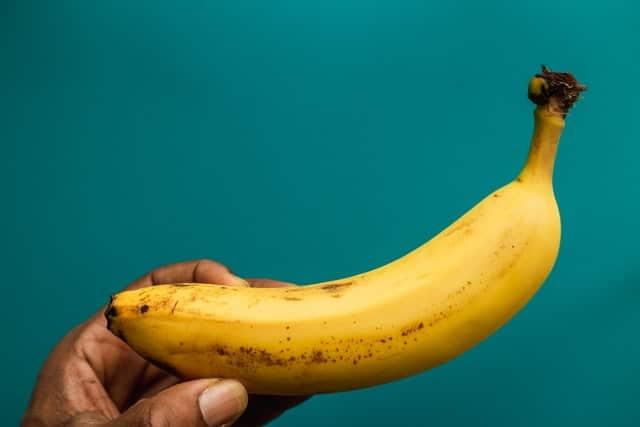 dark skinned hand holding a yellow banana