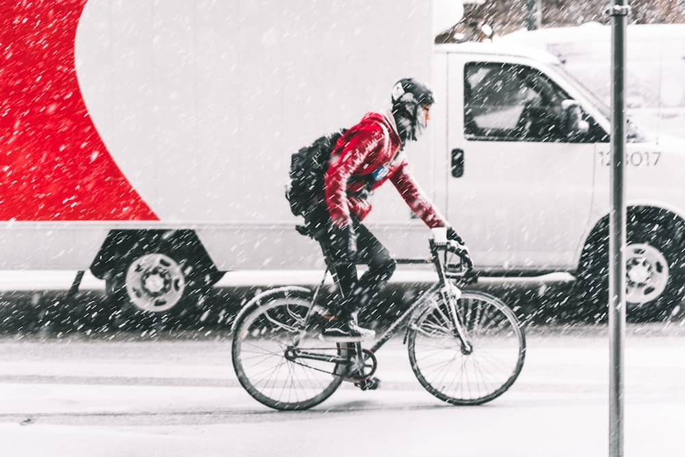 man riding a bike during a winter snowstorm