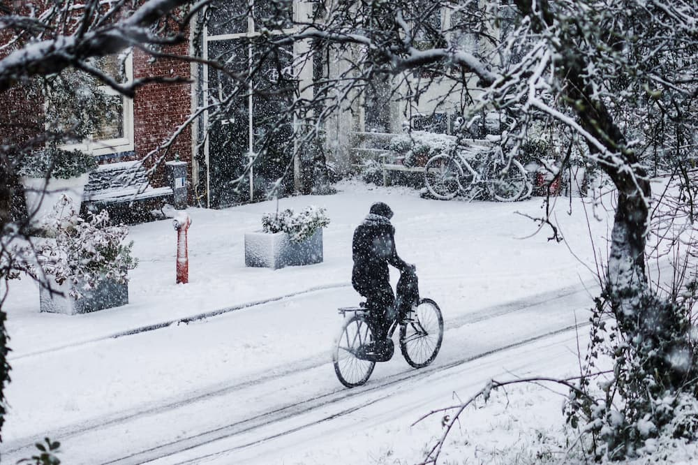 woman riding bicycle on snowy street