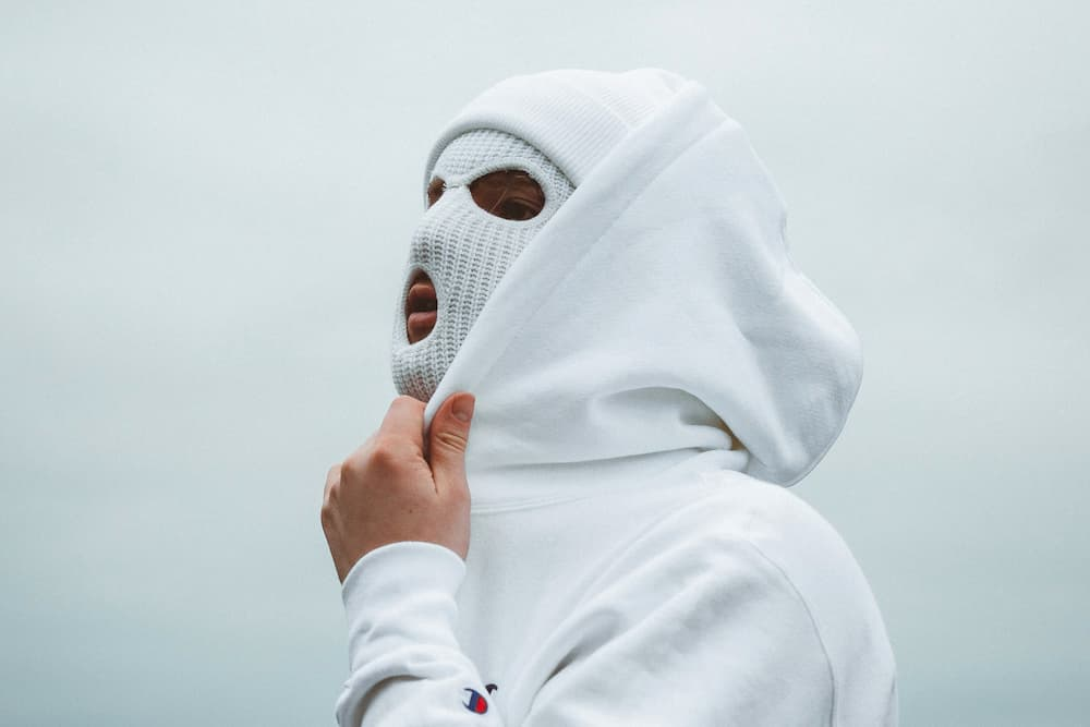 man in white hoodie and white balaclava preparing for bicycle ride in winter